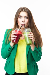 Healthy Food Eating. Smiling Woman Drinking Both Green and Red Detox Vegetable Smoothie. Posing in Green Jacket Over White.Vertical Image