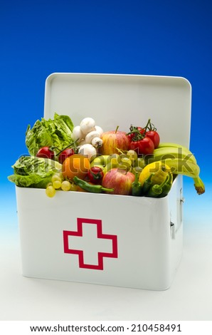 Healthy food. First aid box filled with fresh fruits and vegetables on blue background.