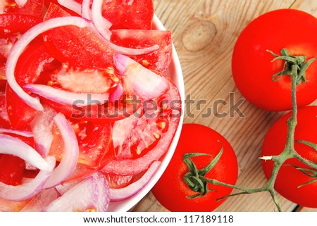 healthy food : fresh tomato salad with onion in white bowl over wood