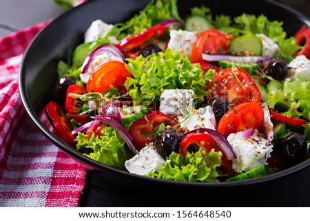 Healthy food. Greek salad with cucumber, tomato, sweet pepper, lettuce, red onion, feta cheese and olives.