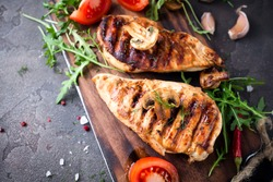 healthy food - grilled chicken with vegetables on a wooden board