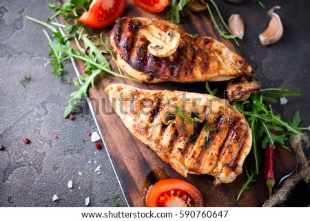 healthy food - grilled chicken with vegetables on a wooden board #590760647