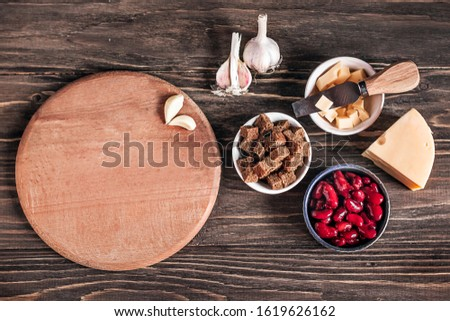 Healthy food: healthy food source against a wooden background. Ingredients for cooking: red beans, hard cheese, crackers, brown bread, garlic. Copy space. Place for text on a cutting board.