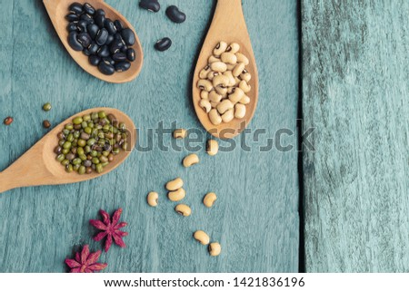Healthy food high protein dry legumes of different types in brown wooden spoons on old wooden background. Above view seed beans on blue wood background. cereal dry of lentils.