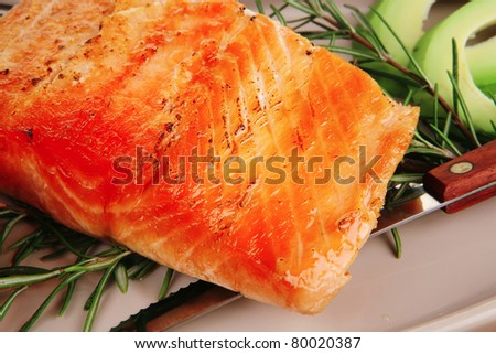 healthy food: hot baked salmon piece served over glass plate on wood