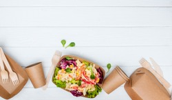 Healthy food in disposable eco friendly food packaging. Vegetable salad in the brown kraft paper food containers on white wooden background with blank space for text. Top view, flat lay.