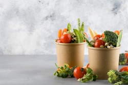 Healthy food in disposable eco friendly food packaging. Vegetables in the brown paper food containers on blue background. copy space