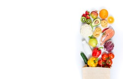 Healthy food in paper bag fruits, vegetables, milk, pasta and fish on white background. Healthy food background. Shopping food supermarket, meal and nutrition plan concept. Top view and copy space