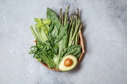 Healthy food ingredients gree vegetables and fruits on bamboo tray on gray background