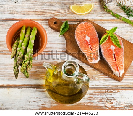 Healthy food  ingredients on a wooden table - salmon, vegetables , lemon and olive oil
