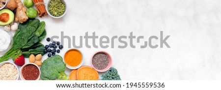 Healthy food ingredients. Top view corner border on a white marble banner background. Copy space. Super food concept with green vegetables, berries, whole grains, seeds, spices and nutritious items. Foto stock ©