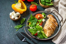 Healthy food. Ketogenic diet lunch. Grilled chicken fillet with fresh vegetable salad, spinach and feta on a dark stone background. Copy space.