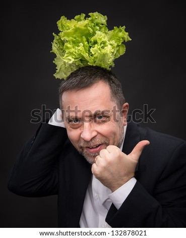 Healthy food. Man holding  lettuce and shows the symbol OK