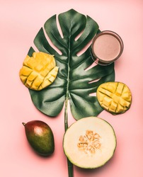 healthy food, melon, mango and smoothies are laid out on a monstera leaf, on a pink background, flat lay
