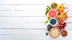 Healthy food on a white wooden table. Fresh vegetables, fruits, nuts, berries, mushrooms. Top view. Free space for text.