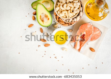 Healthy food. Products with healthy fats. Omega 3, omega 6. Ingredients and products: trout (salmon), flaxseed oil, avocado, almonds, cashews, pistachios. On a white stone table. Copy space top view #683435053