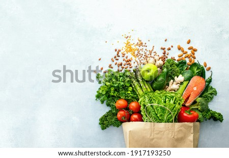 Healthy food shopping or delivery concept, top down view on a variety of fresh produce in a paper bag, composition with copy space for a text