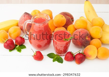 Healthy food. Strawberry banana smoothie with mint in a glass and pitcher on white wooden background. Fresh fruits bananas, peaches and apricots background. Selective focus.