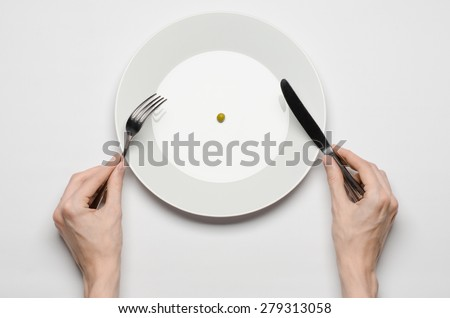 Healthy food theme: hands holding knife and fork on a plate with green peas on a white table top view #279313058
