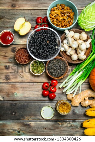 Healthy food. Variety of organic vegetables and mushrooms . On a wooden background. #1334300426