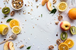 Healthy food vegan breakfast nutrition concept, fresh summer fruits nuts granola seeds on white background, organic super food on table, detox diet for health care, top close up view, copy space