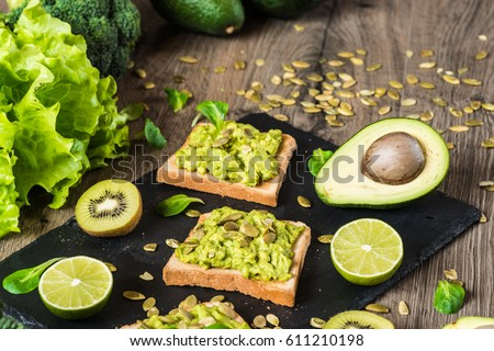 Healthy food. Vegan sandwiches with fresh vegetables on wooden background. #611210198