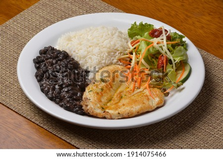 Healthy food with chicken breast, beans, rice, vegetable salad on a white plate on wooden table. Brazilian cuisine.