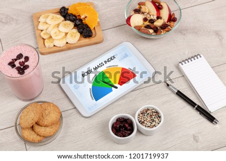 Healthy food with tablet on a wooden background with words Body Mass Index. Health concept. #1201719937
