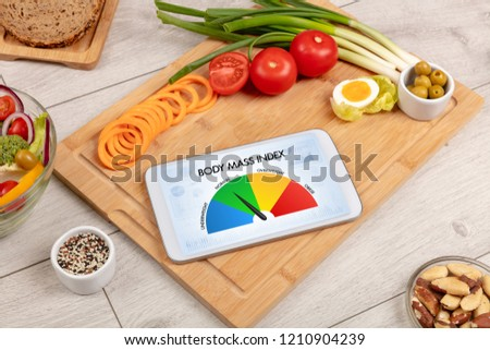 Healthy food with tablet on a wooden background with words Body Mass Index. Health concept. #1210904239