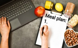 Healthy foods. Female hands are writing in a clipboard MEAL PLAN next to a laptop, fruits,nuts on a gray concrete background. Healthy food and diet concept. Flat lay.