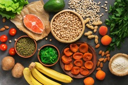 Healthy foods high in potassium. A variety of legumes, salmon, fruits, vegetables, dried apricots, seaweed chuka and nuts on a dark background. Top view, flat lay