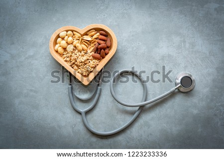 Healthy Foods. Mixed nuts in heart shape and stethoscope with nuts for diet on a concrete background. Different kinds of tasty and healthy nuts. Top view and copy space.  Healthy Concept
