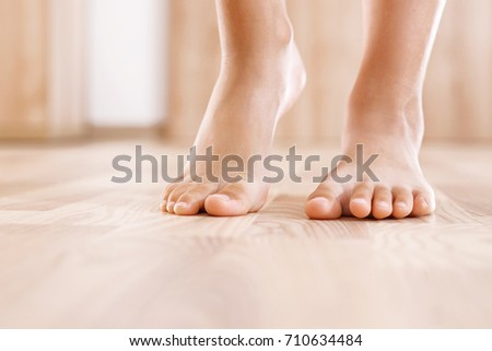 Healthy foot baby.  Feet of baby's naked against the background of the wooden floor  #710634484