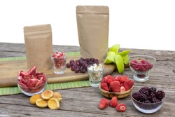 Healthy freeze dried fruits, strawberries, raspberries, blackberries, blueberries and organic paper package on vintage table background isolated on white.