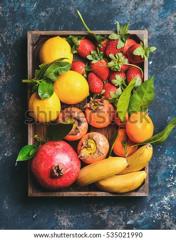 Healthy fresh fruit variety. Oranges, lemons with leaves, pomegranate, bananas, strawberries and persimmon in wooden box over dark blue plywood background, top view, vertical composition - Shutterstock ID 535021990
