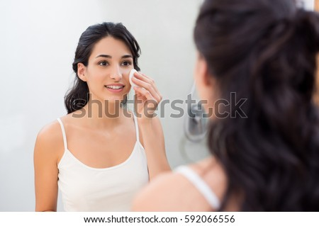 Healthy fresh girl removing make up from her face with cotton pad. Smiling girl cleaning her face in bathroom. Beautiful healthy woman making scrub on her face.