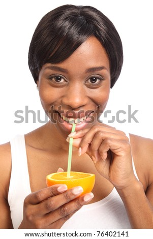 Healthy fresh orange drink using a straw straight from a fruit slice, by beautiful young black woman with a lovely smile.