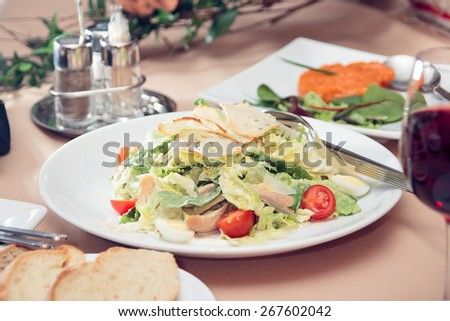 Healthy fresh salad on white plate in restaurant