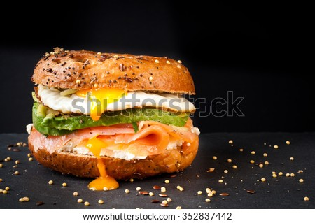 Shutterstock Healthy freshly baked bagel filled with smoked salmon lox and topped with avocado and an egg. Served on a gray slate table against a dark background.