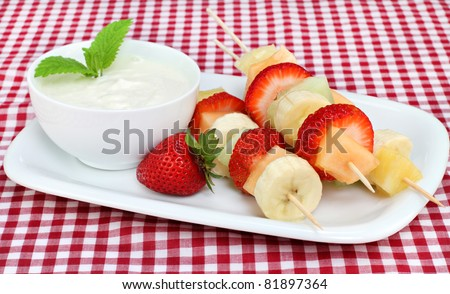 Healthy fruit kabobs with yogurt dip, garnished with fresh mint leaves.