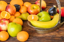Healthy fruit on a wooden background. Stylish, ornate metal basket full of fresh fruit.   concept of proper nutrition full of vitamin
