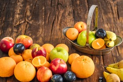Healthy fruit on a wooden background. Stylish, ornate metal basket full of fresh fruit. Place for text