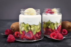 Healthy fruit snack with raw raspberry and kiwis and yoghurt layered in glass on dark background