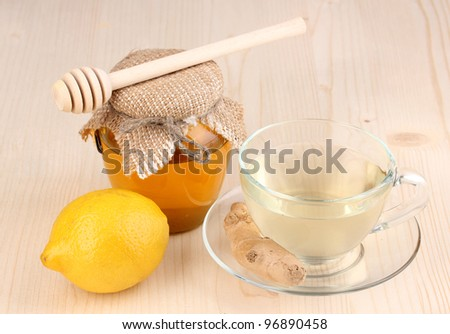 Healthy ginger tea with lemon and honey on wooden background