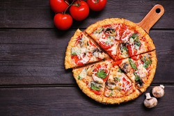 Healthy, gluten free cauliflower crust pizza with tomatoes, mushrooms and spinach. Top down view with cut slices. Table scene on a dark wood background.