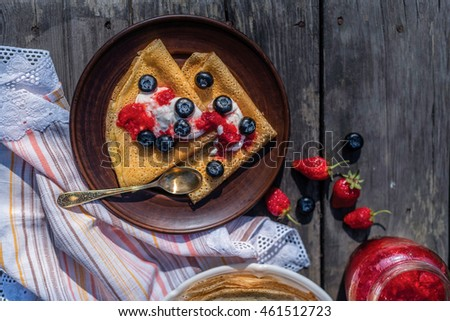 Healthy gourmet breakfast. Homemade pancakes, crepes with sour cream with blueberry and strawberry jam. Organic pancakes lie on a wooden table in the orchard. #461512723