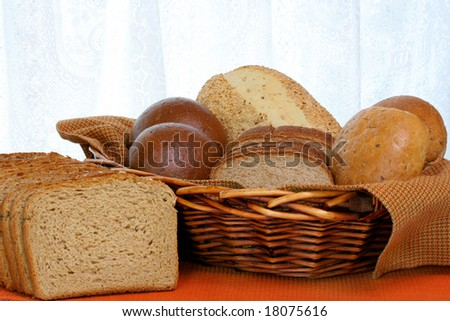 Healthy grain breads and rolls fill a wicker basket.