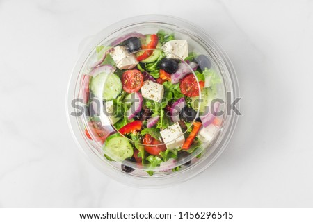 Healthy greek salad in plastic package for take away or food delivery on a white marble background. top view