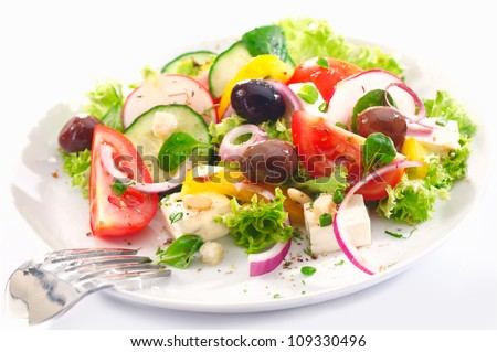 Healthy Greek salad served for lunch with crisp leafy greens, olives, feta, onion , tomato, cucumber and radish on a white background - stock photo