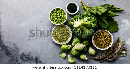Healthy Green food Clean eating selection Protein source for vegetarians: brussels sprouts, broccoli, spinach, spirulina, green peas on gray concrete background copy space